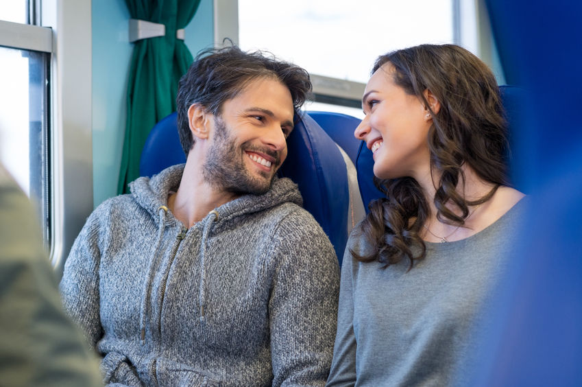 38774787 - closeup of happy young couple traveling by train together. they are looking at each other while smiling and enjoy the trip. they are sit on blue seats in a train's coach.